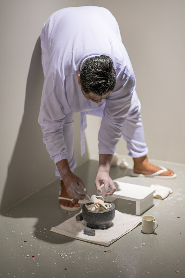 Ezzam Rahman  i should have kissed you when we were alone  (performance still) 2019 Painted wooden stools, granite urn, crushed porcelain from 38 white-glazed ceramic mugs, granite pestle and mortar, vintage medicinal glass jar, body paint Dimensions Variable