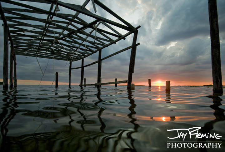 the frame of a crab shanty in Frenchtown, Maryland is silhouetted at sunset