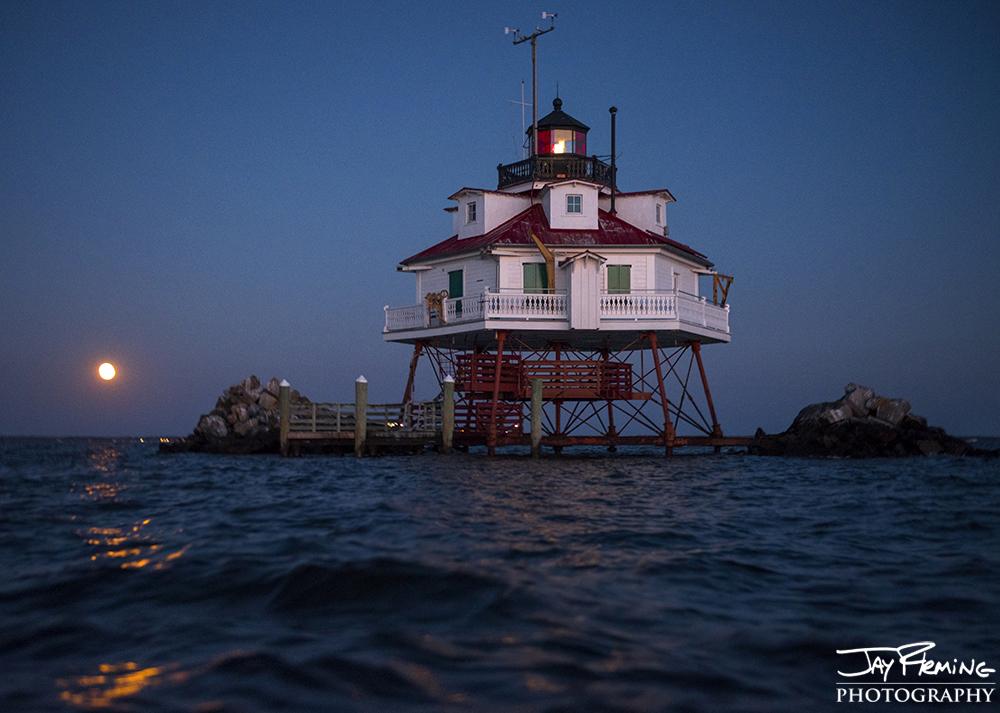 the November full moon rises behind Thomas Point Shoal Light. Annapolis, Maryland