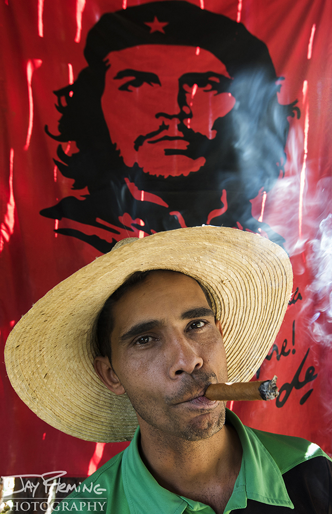 A Vinales plantation owner smoking a cigar in front of a flag showing Che Guevara - an icon of the Cuban revolution.