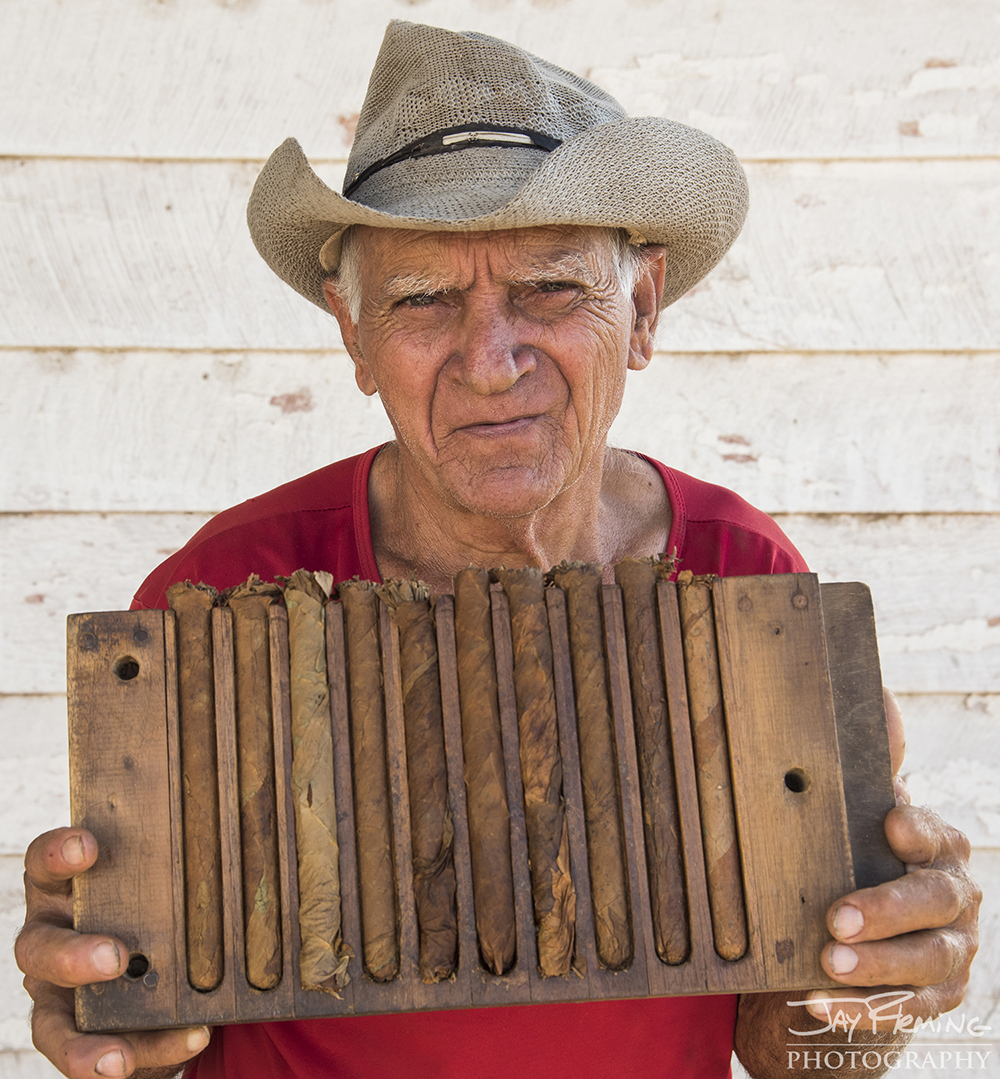 Mamino Gomez, 81, has worked on the Alejandro Robiano Plantation for sixty years. In this photograph, he holds a wooden cigar mold that he uses to shape his hand rolled cigars. Pinar del Rio.