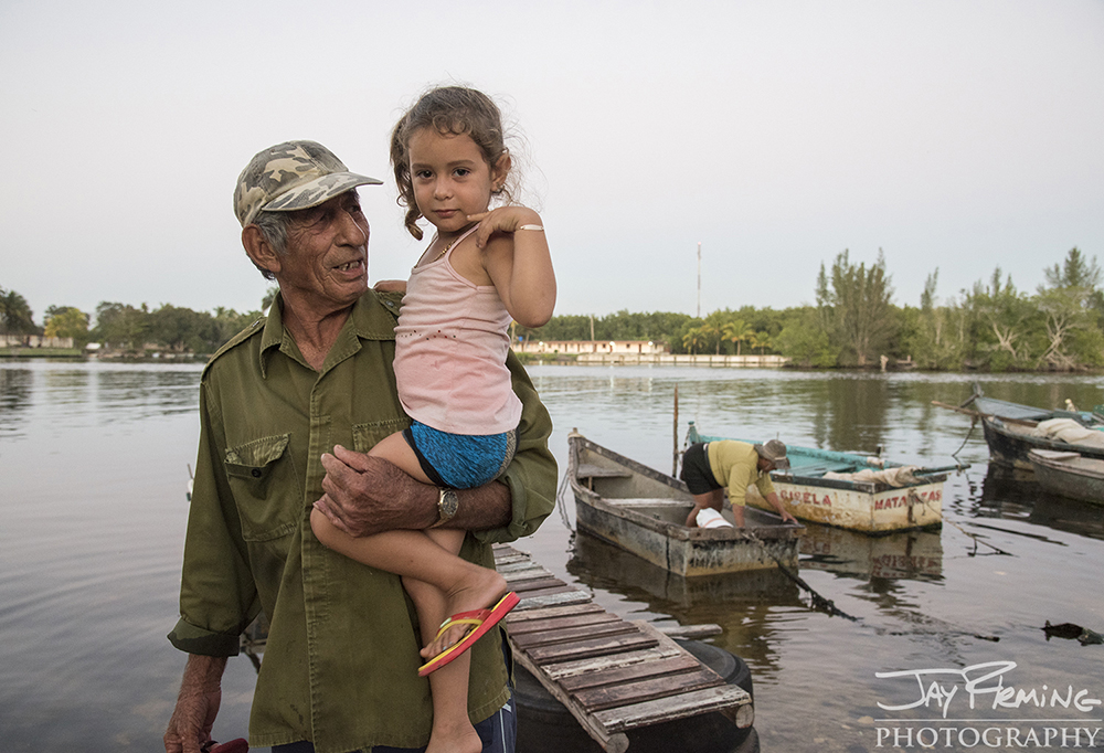 A Playa Larga fisherman and his granddaughter after a day on the water