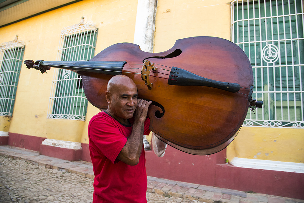 Trinidad musician carrying upright bass to a performance at a restaurant