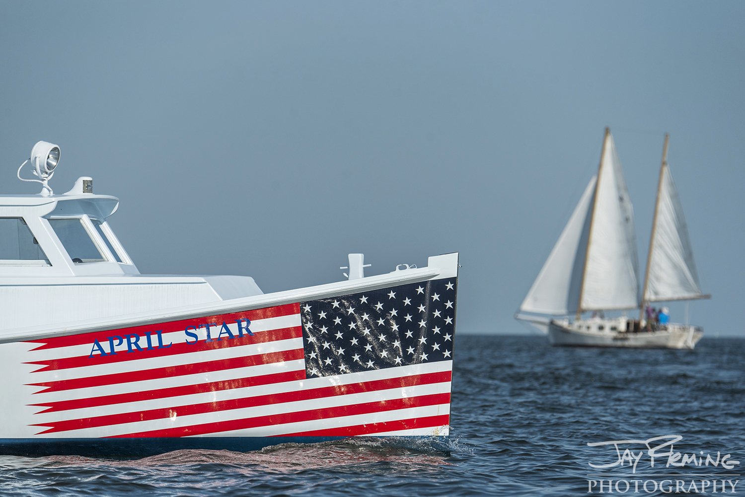 The classic roundstern workboat  April Star  out of Scott's Cove Marina on Deal Island watches the race with passengers.