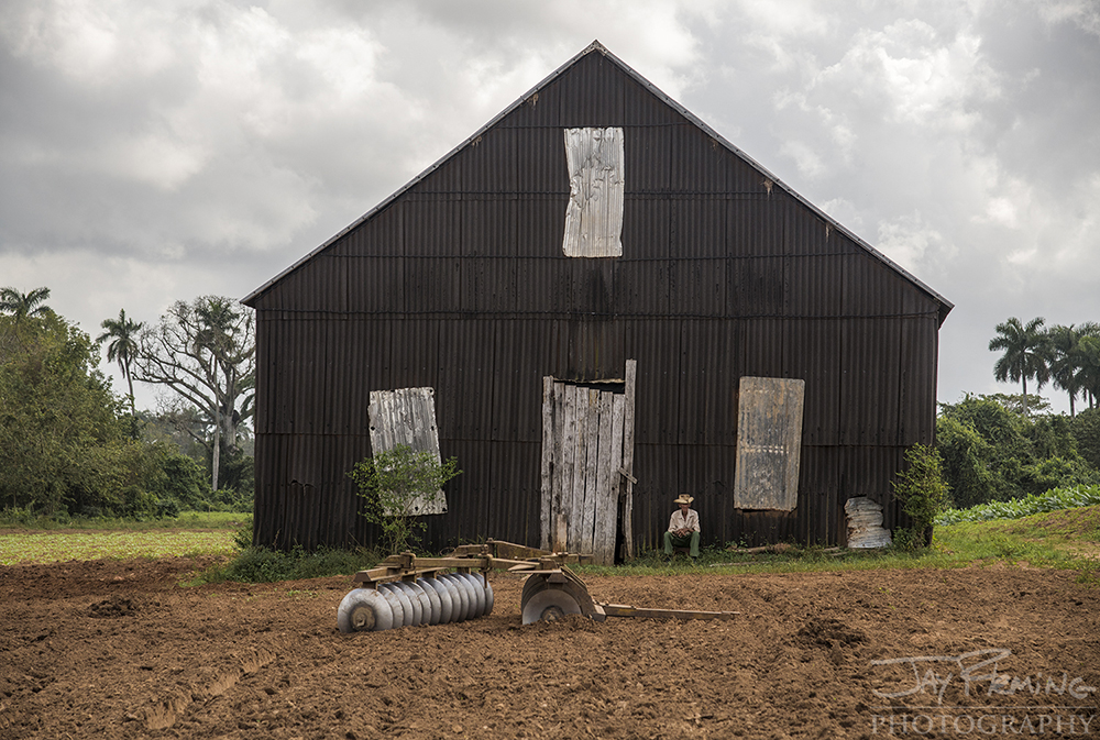 Cenavio Gonzalez, 83 years old, takes a break from work in front of his tobacco barn just outside of San Luis.