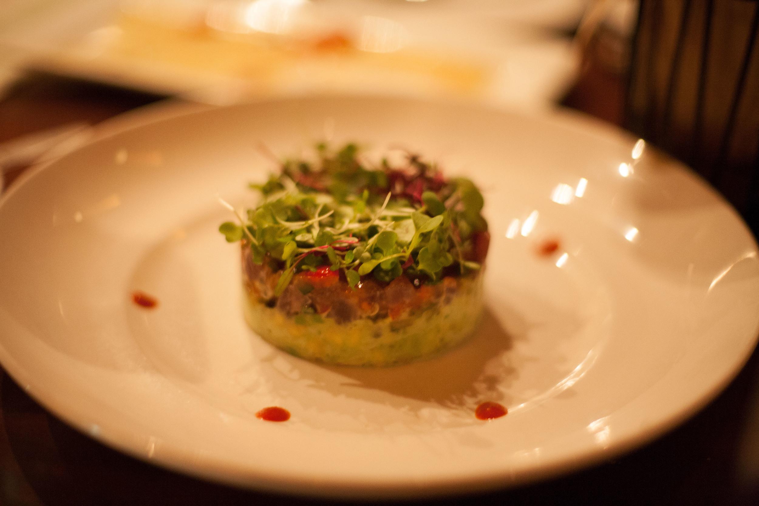 Ahi Tuna Tartare layered with wasabi-avocado mousse & tropical salsa, served with Hawaiian sea salt crisps.