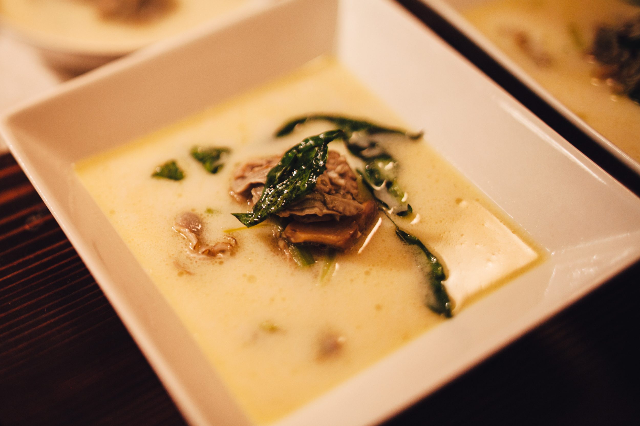 Oyster bisque with fresh Gulf oysters in a shellfish-based broth, with a hint of saffron and topped with grilled oyster mushrooms and a drizzle of basil oil.