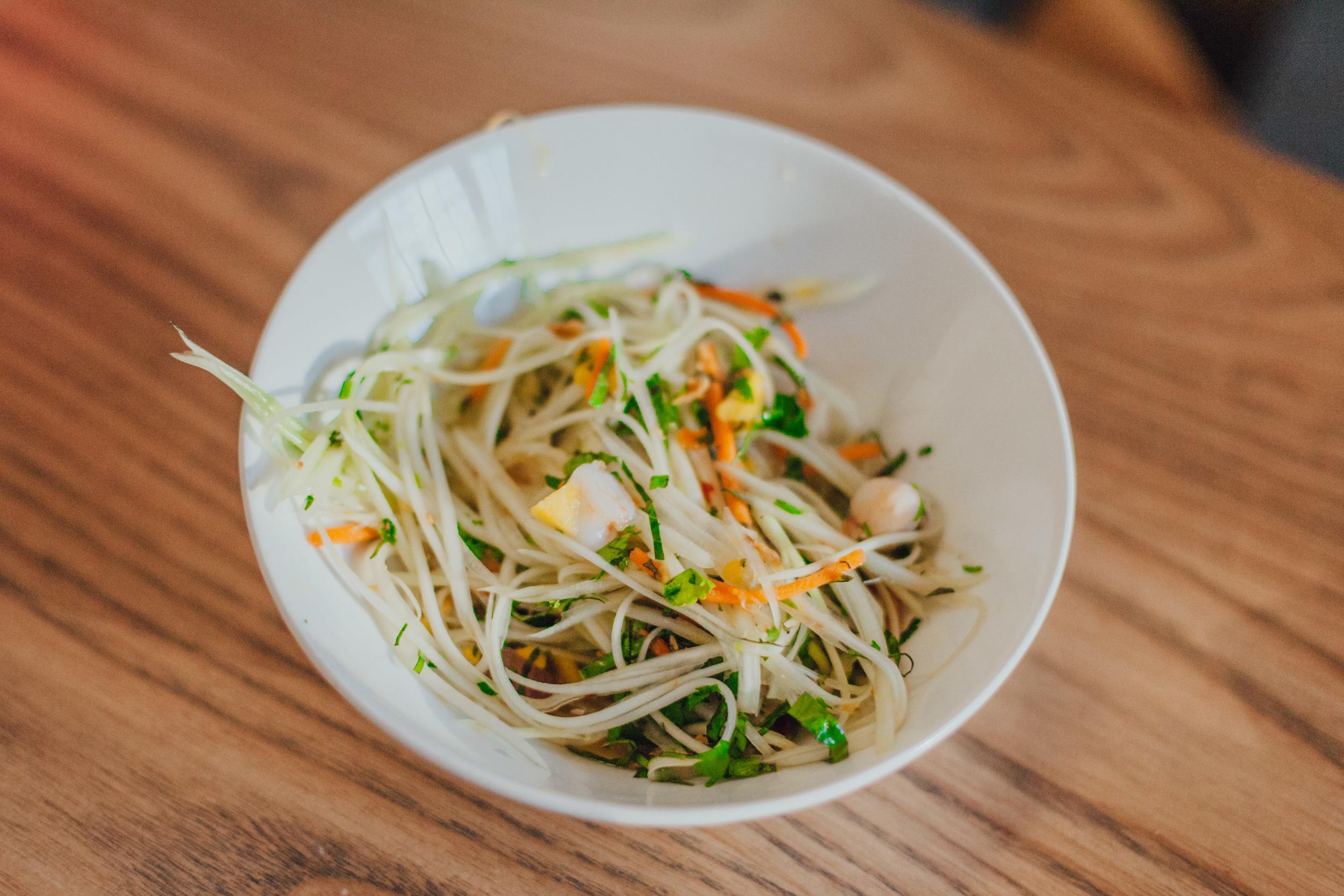 Green Papaya & Shrimp Salad:Poached shrimp, green papaya, carrots, basil, and cilantro tossed in spicy Vietnamese vinaigrette dressing. Topped with mango salsa, fried shallots, and roasted peanuts.