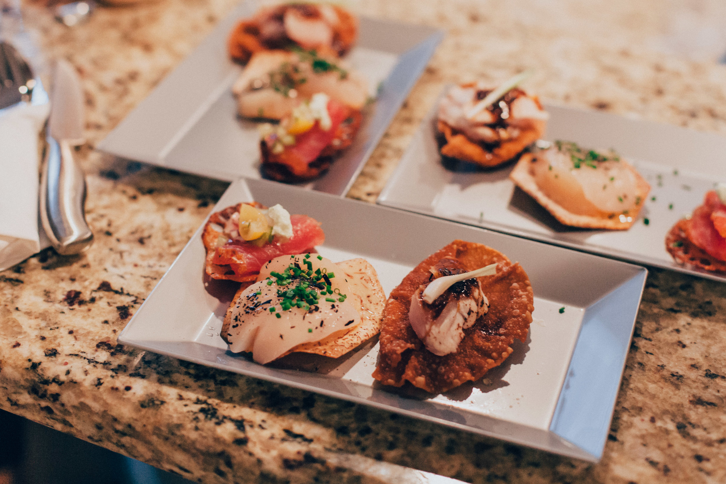 Jalapeno and cucumber tuna sashimi atop lotus root crisps | Truffle-orange Japanese scallops atop taro crisps | Red snapper sashimi with black bean sauce atop wonton crisps