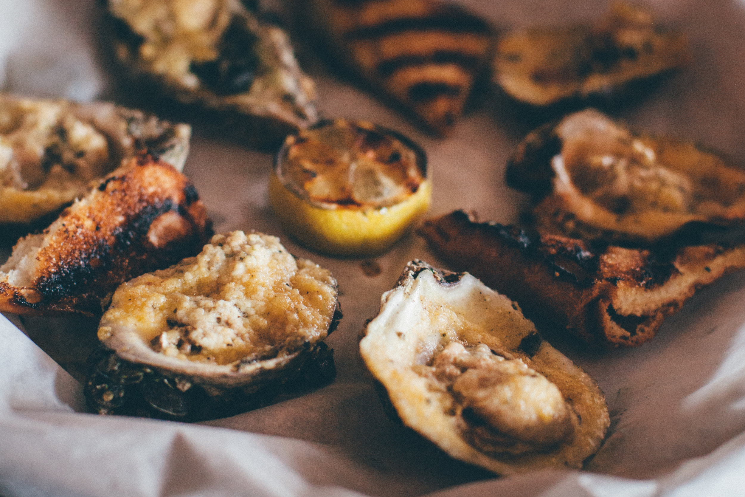 Char-grilled oysters, topped with Romano and Parmesan cheese and Roux compound butter.