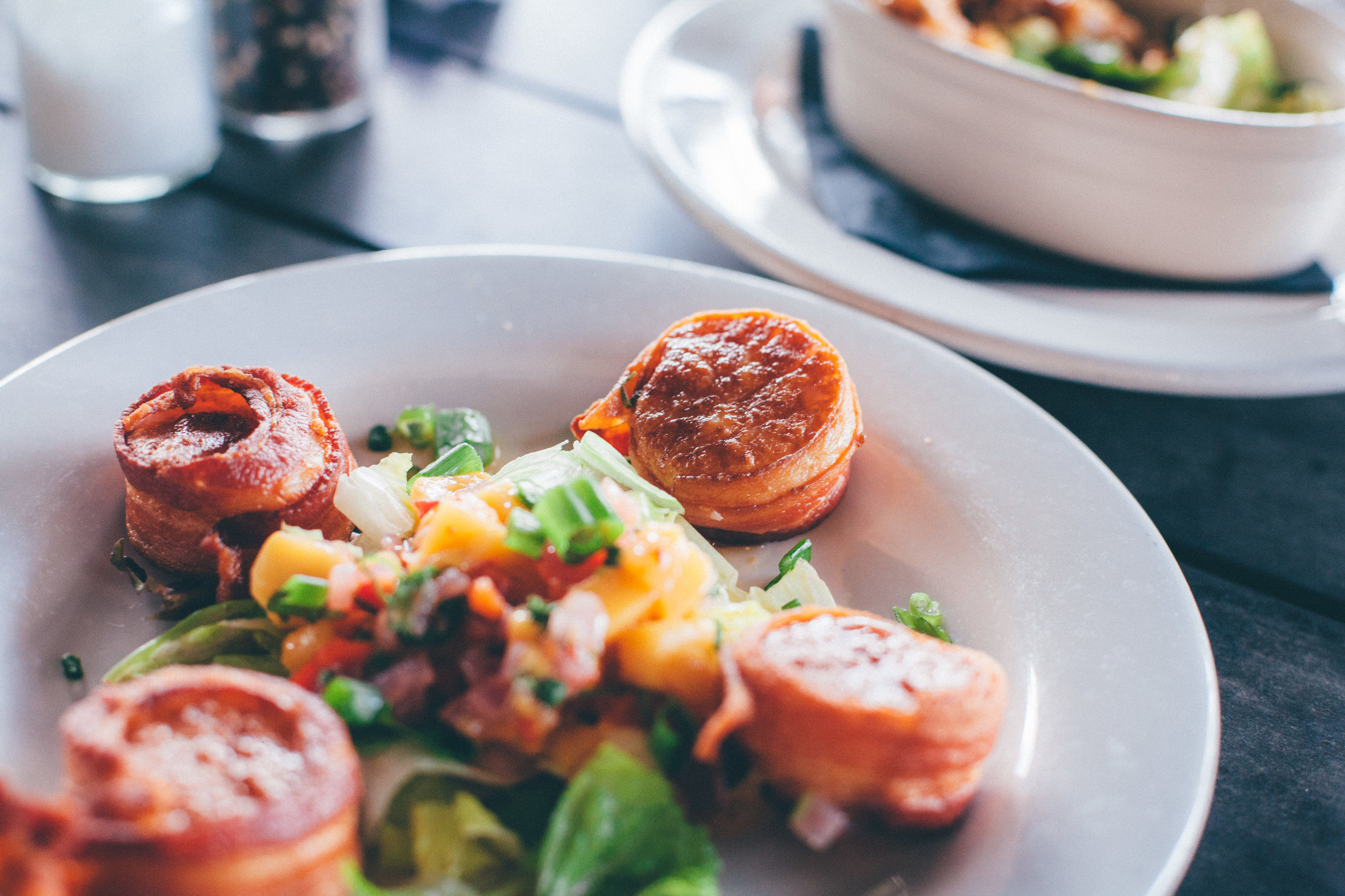 Applewood Bacon-Wrapped Scallops:Four Georges Bank Scallops wrapped in Applewood bacon and topped with mango salsa