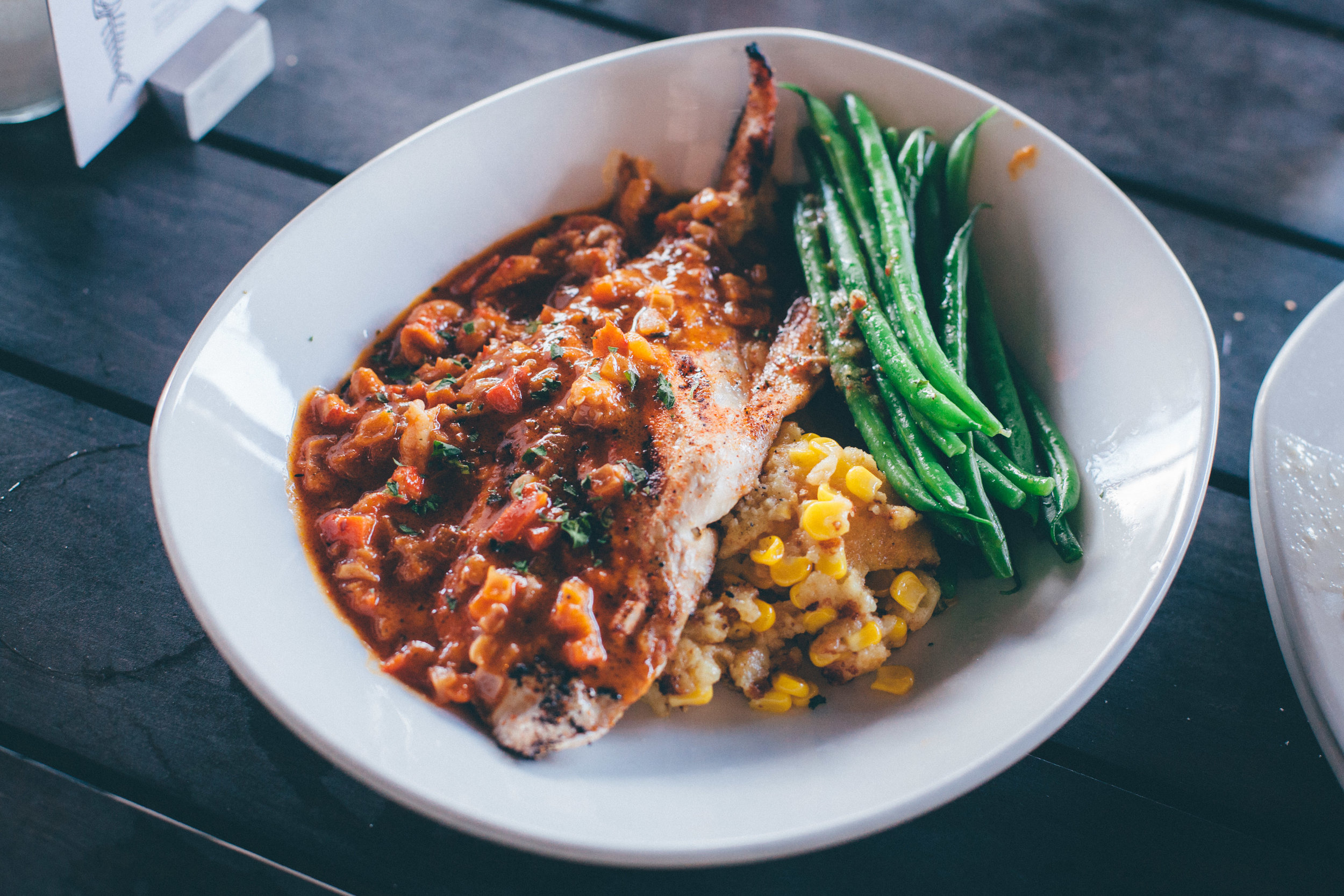Creole-Style Redfish:A mild, sweet flavor with a medium firm texture. Wood-grilled and topped with crawfish and a Creole-style sauce, served with sweet corn spoonbread and french green beans