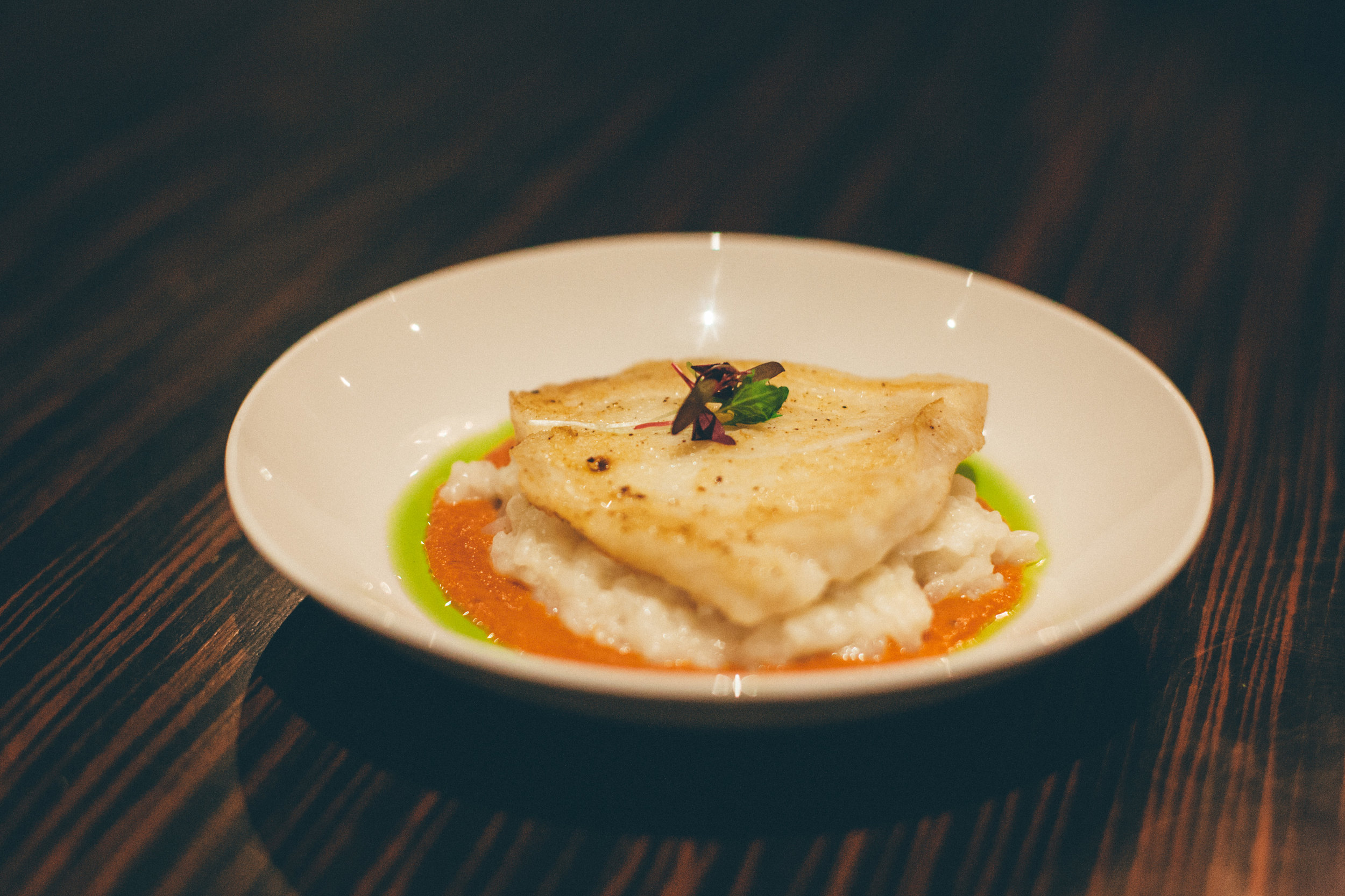 Pan-Seared Chilean Sea Bass: Parmesan risotto, roasted tomato fondue and basil-infused oil