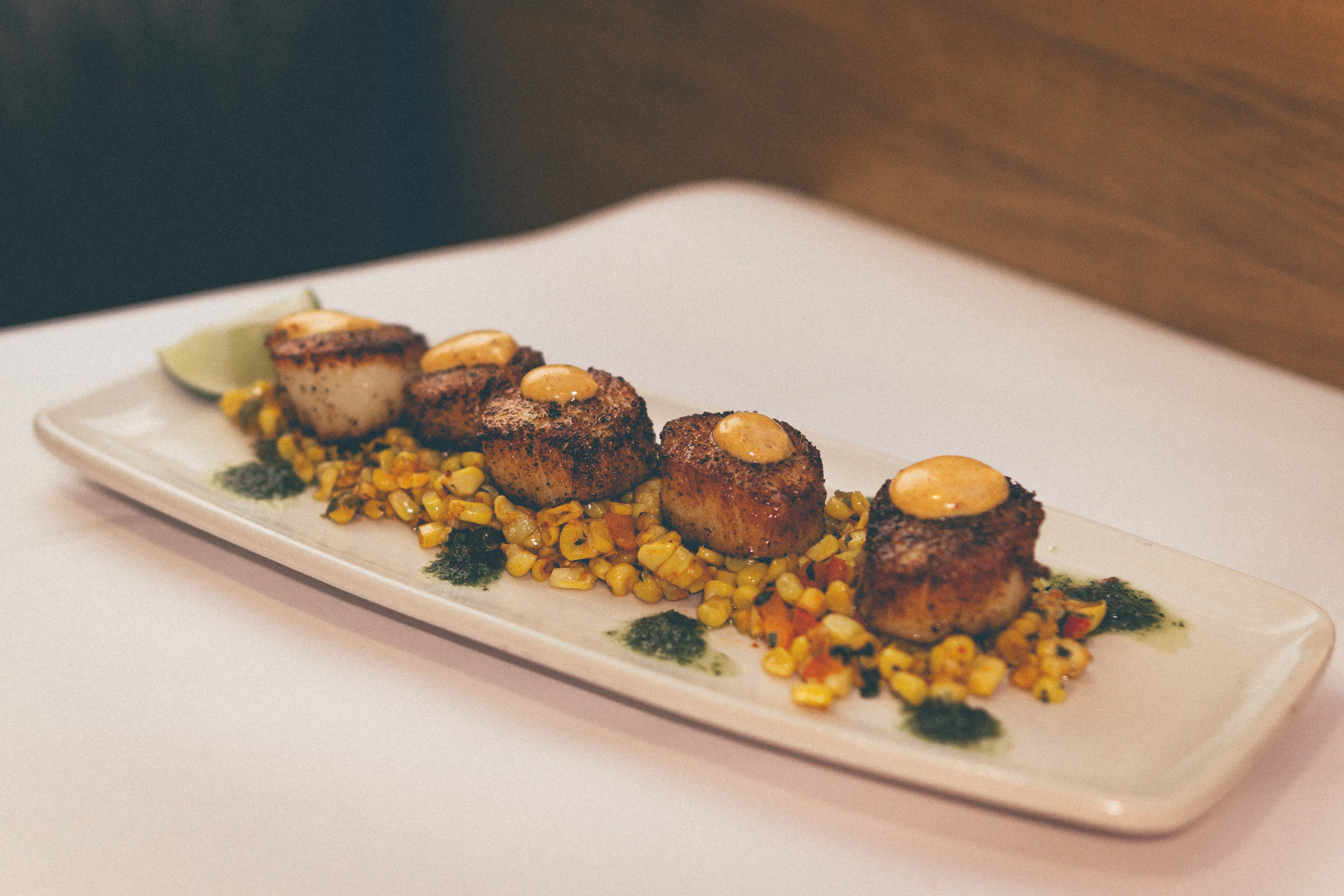 Fresh Dayboat Scallops Elote: Fresh Dayboat scallops served on a bed of Mexican-style street corn, paired with Chimichurri & smoky Chipotle aioli.