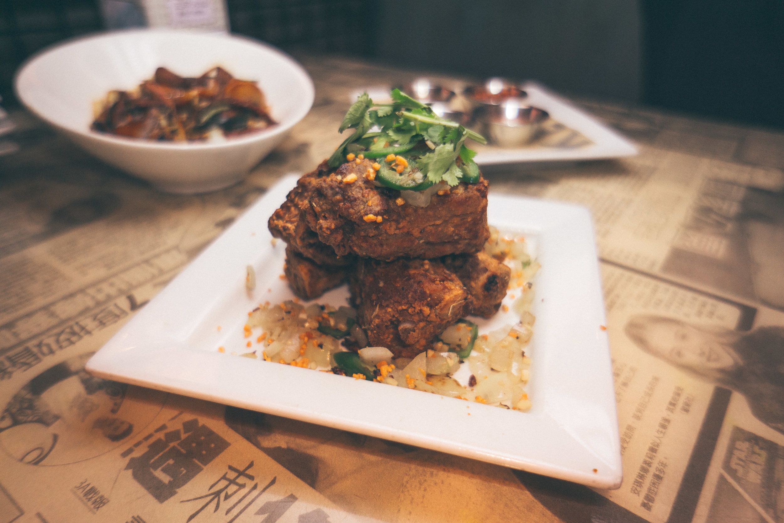 Salt-N-Pepa Ribs: Double-fried crispy pork riblets tossed in ginger, Serrano peppers, garlic & onions