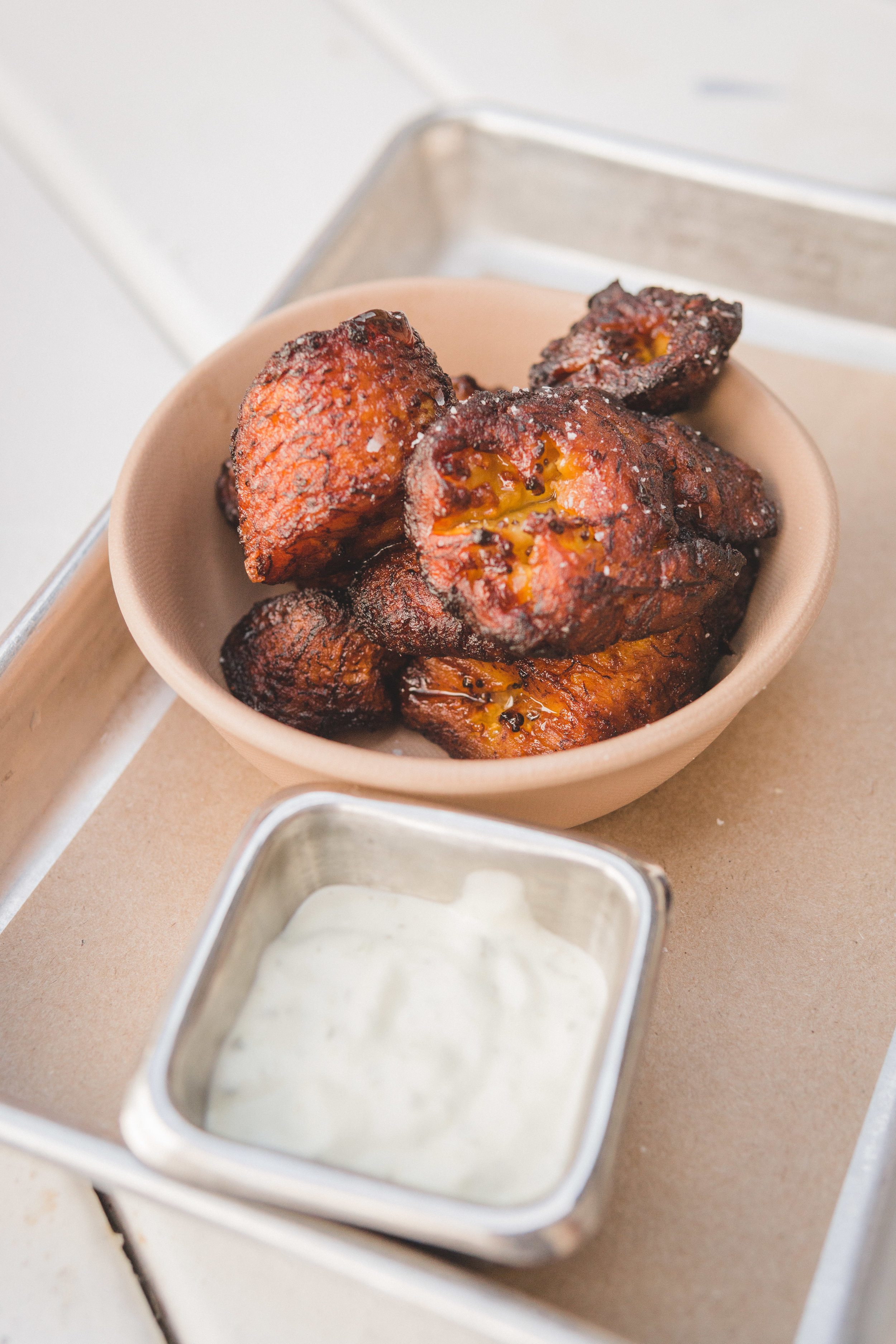 Plantains: Tossed in salt & cayenne pepper, served with a creamy gordita sauce