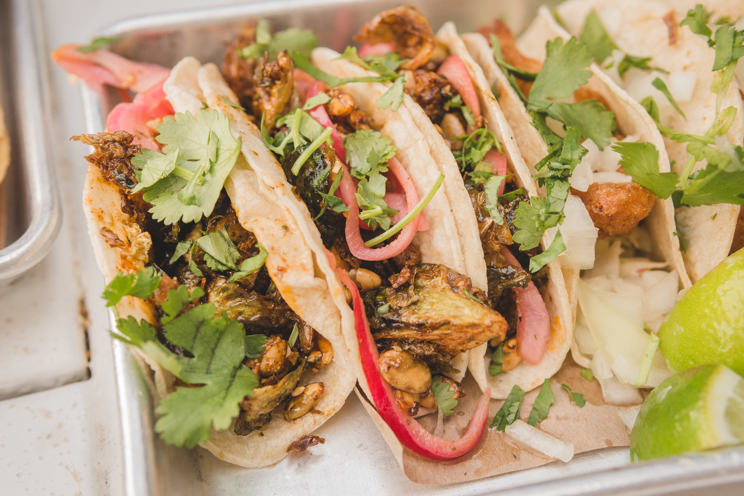 The latest secret taco - Crispy Brussels Sprouts: honey chipotle glazed crispy brussels sprouts served on a bed of spicy curry carrot puree and garnished with candied pepitas and pickled onions.