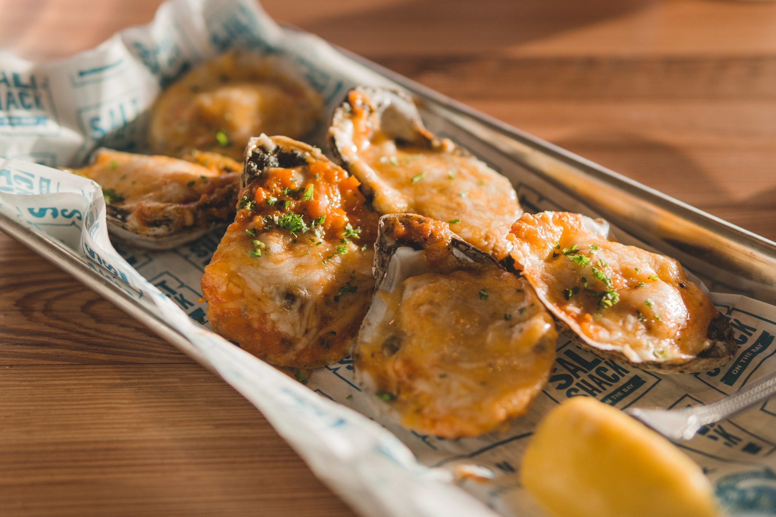 """1/2 dozen oysters, baked """"island-style"""" with sofrito, Cabot cheese & cilantro"""