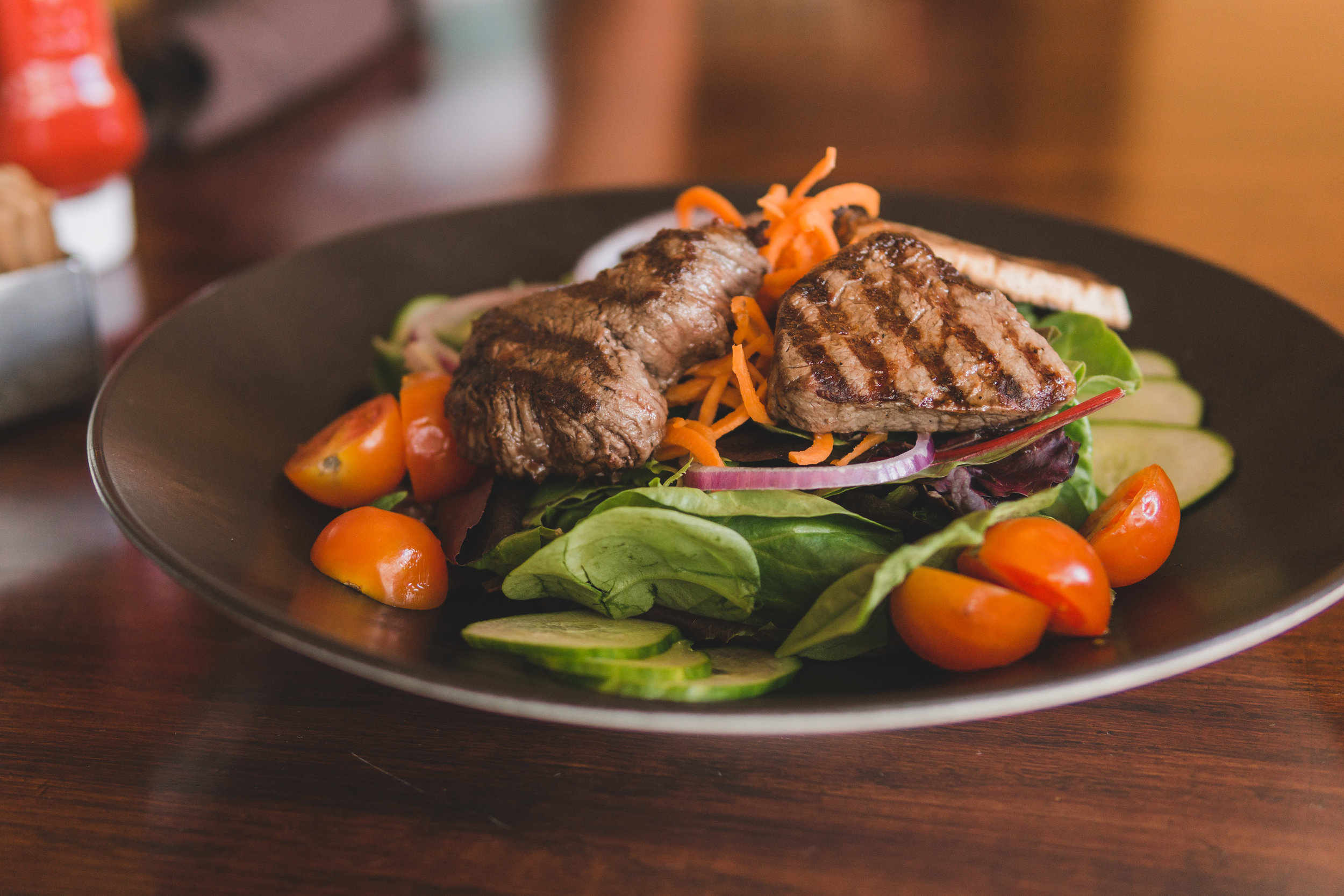 Farmer's Steak Salad: Filet medallions, mixed greens, tomatoes, carrots, onions, cucumber & balsamic vinaigrette dressing