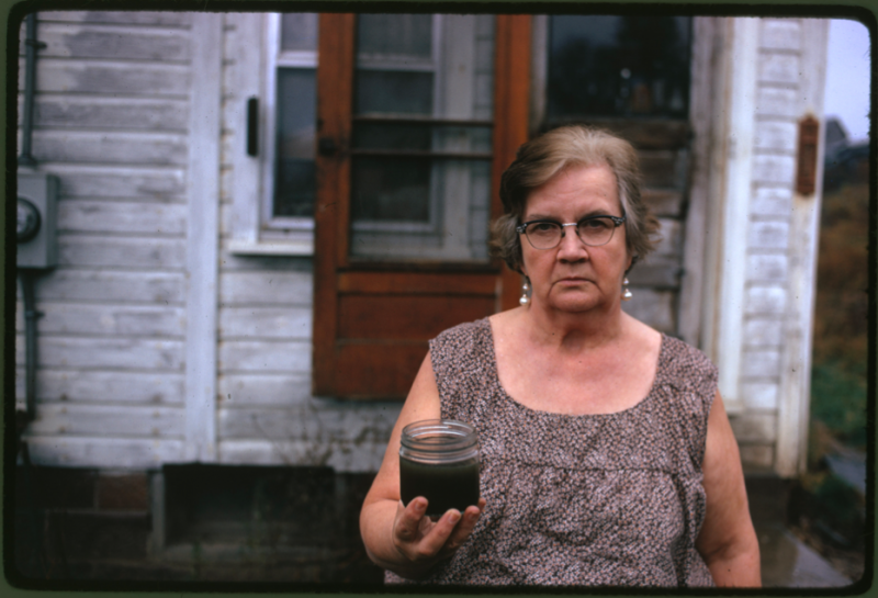 """Mary Workman holds a jar of undrinkable water that comes from her well, and she has filed a damage suit against the Hanna Coal Company. She has to transport water from a well many miles away although the coal company owns all the land around her, and many roads are closed, she refuses to sell."" Erik Calonius, near Steubenville Ohio, October 1973 (412-DA-12346)"