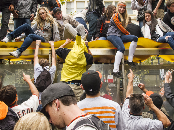 SF Giants Fans on top of a bus shelter. Market Street. San Francisco, CA