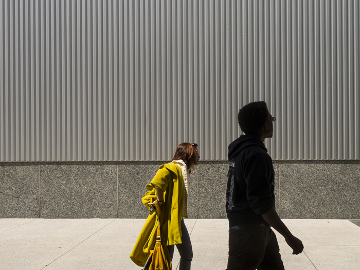 Woman taking her yellow jacket off. Yerba Buena Gardens.San Francisco, CA.