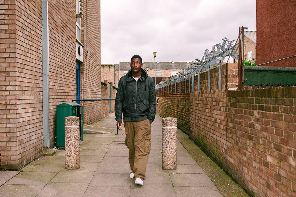 "Amos walking to the youth centre,  Clapton, 2008  A gifted musician and big hearted teen, not long after this photo was taken Amos was kicked out of school over a silly incident with a firecracker, which caused him to be socially excluded and lead him down a risky path where he got involved in gang-related activity. Thankfully this was temporary, and he knows he's lucky to have avoided anything bad happening to him. ""It was hard for us young black boys, a lot of us didn't really believe that we could do more."""