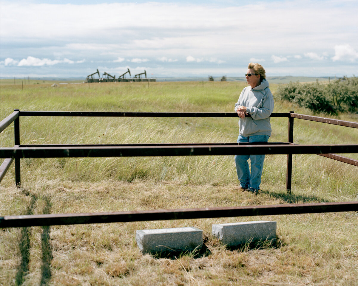 "Carole at her parents' graves, July 2016  Carole is a fourth-generation rancher near Watford City, in the heart of the oil patch. She says, ""People don't understand what this costs the landowners. We all wanted this oil development. We just didn't know what we were in for. Even half of what we got would've been too much. Our way of life has changed. It's never going to be the same… I'm glad that my Mom & Dad didn't live to see this."""