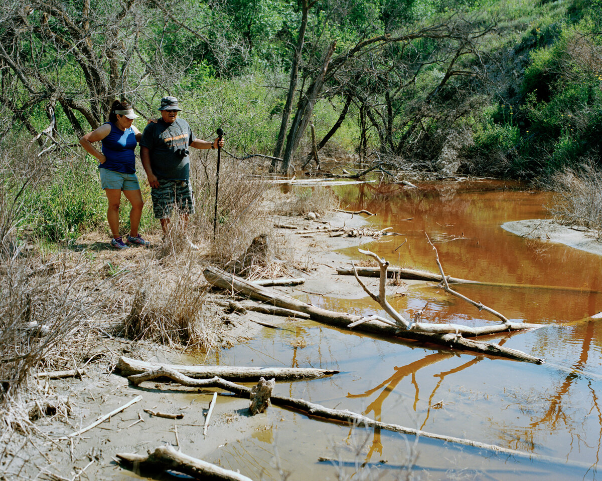 Million gallon saltwater spill site near Bear Den Bay, Ft. Berthold Reservation, July 2015  A year after this toxic wastewater flowed downhill through a ravine to Lake Sakakawea, Lisa & Walter DeVille examine the still-contaminated spill area. Although tribal officials believe their water supply was not affected, a study conducted by Duke University researchers proves otherwise.