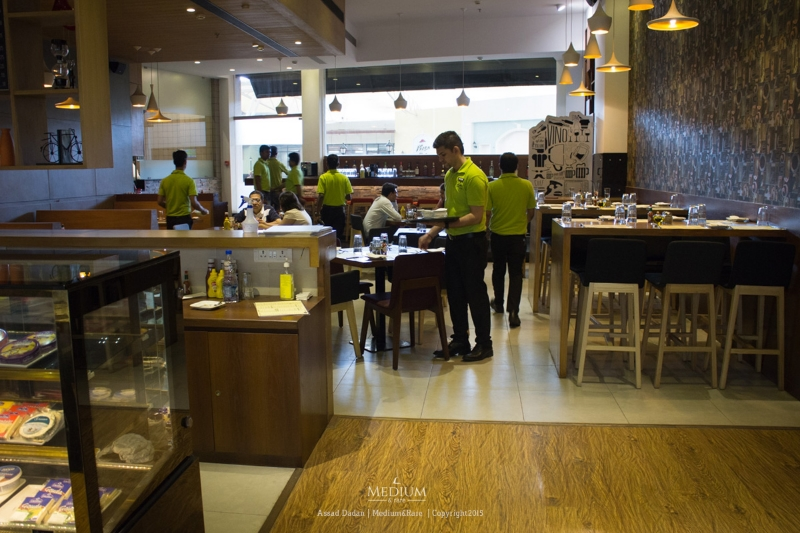 Classic wooden interiors and shades of lime green moving around at 212 All day Cafe & Bar