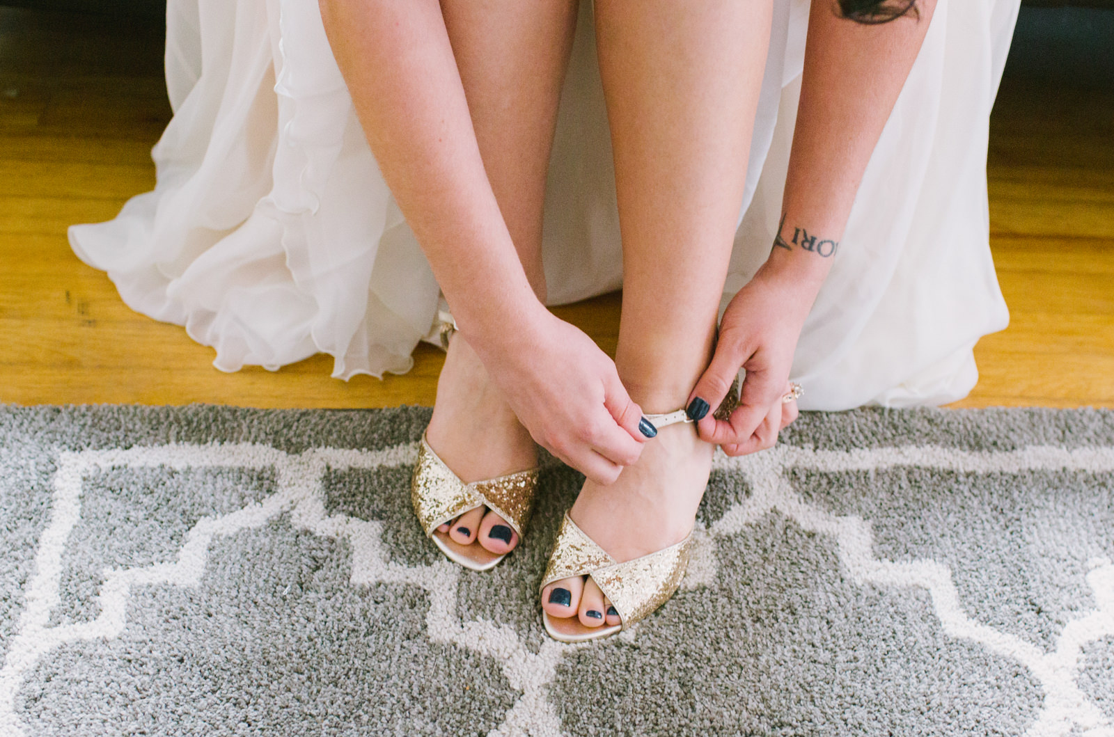 bride putting shoes on before wedding