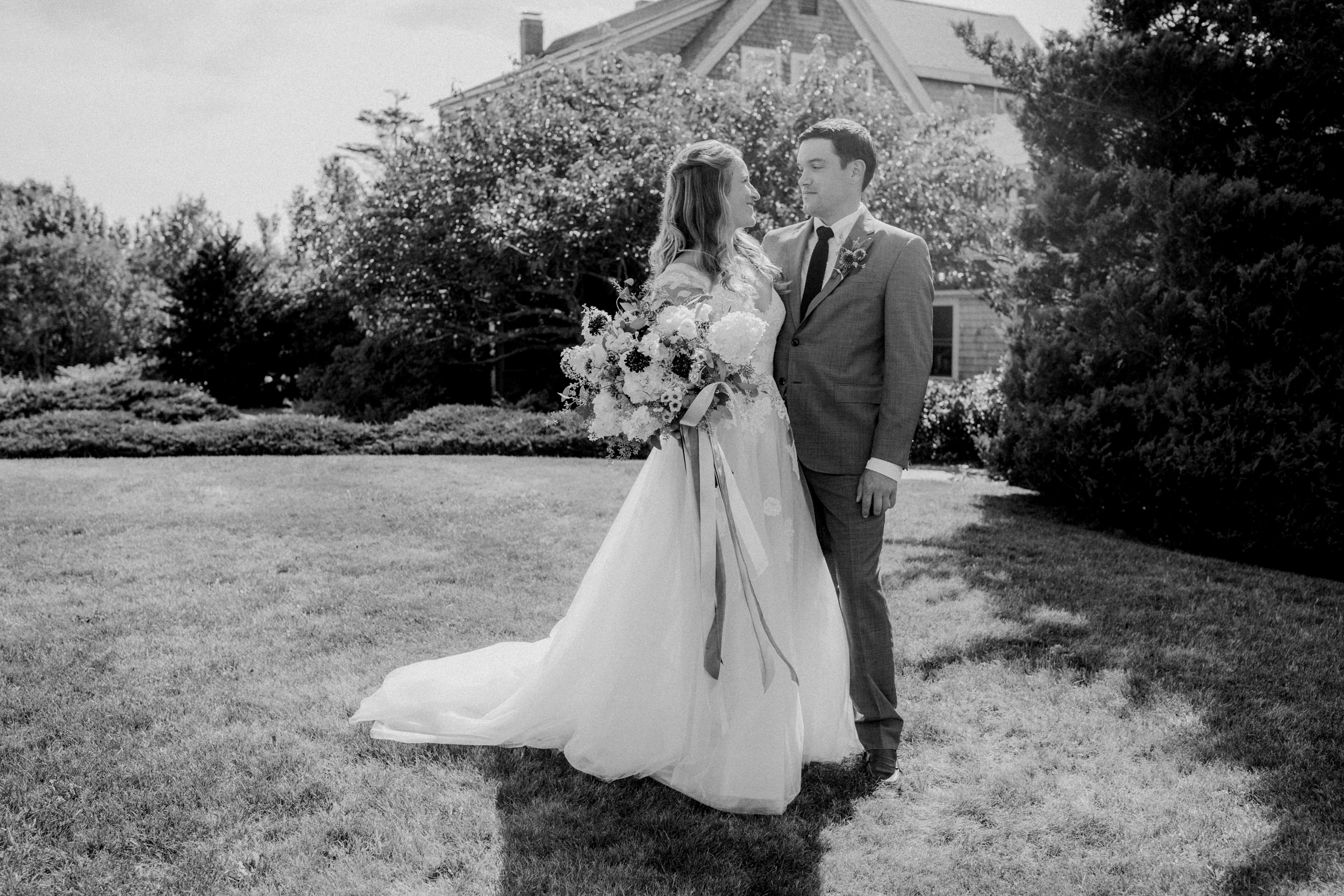 A bride and groom on the lawn of the inn at their mid coast Maine wedding