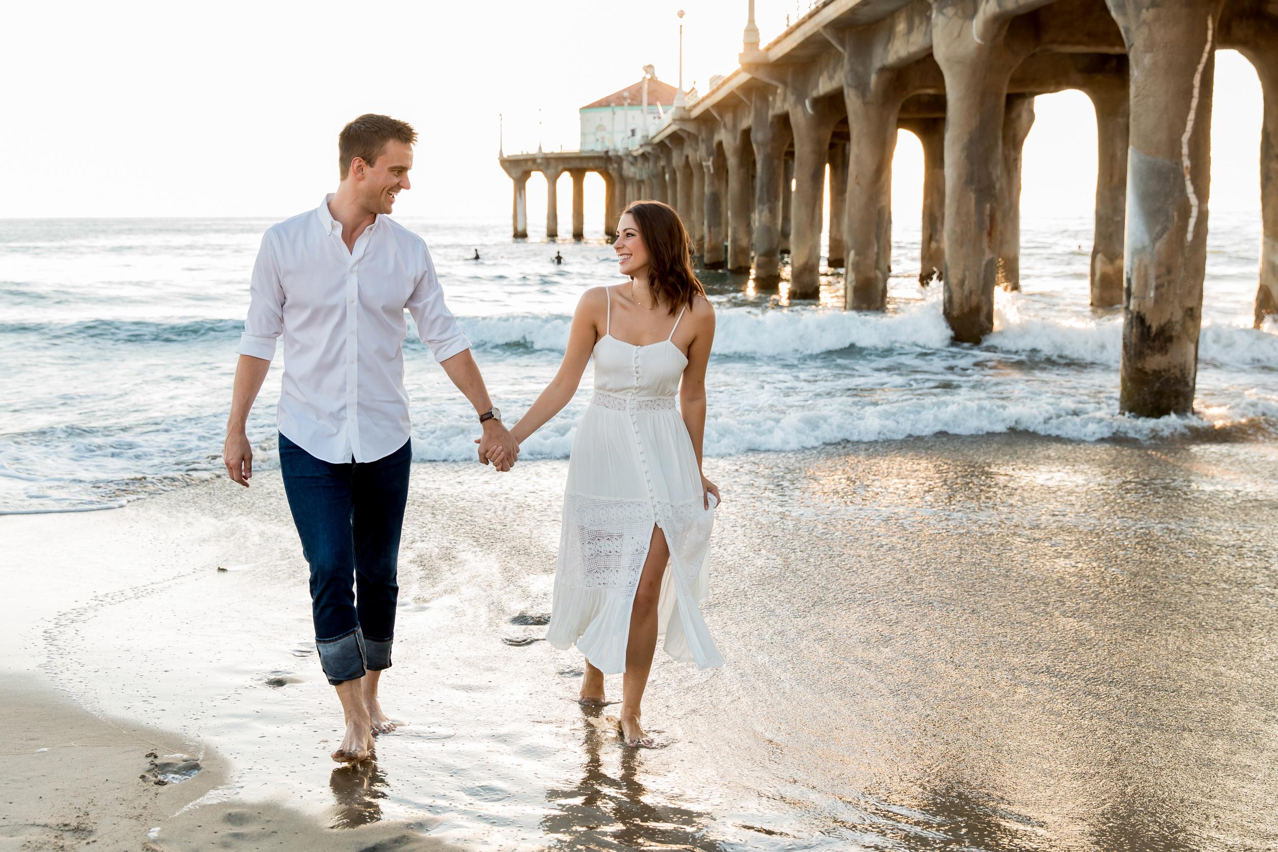 A couple walks on a California beach with the pier behind them