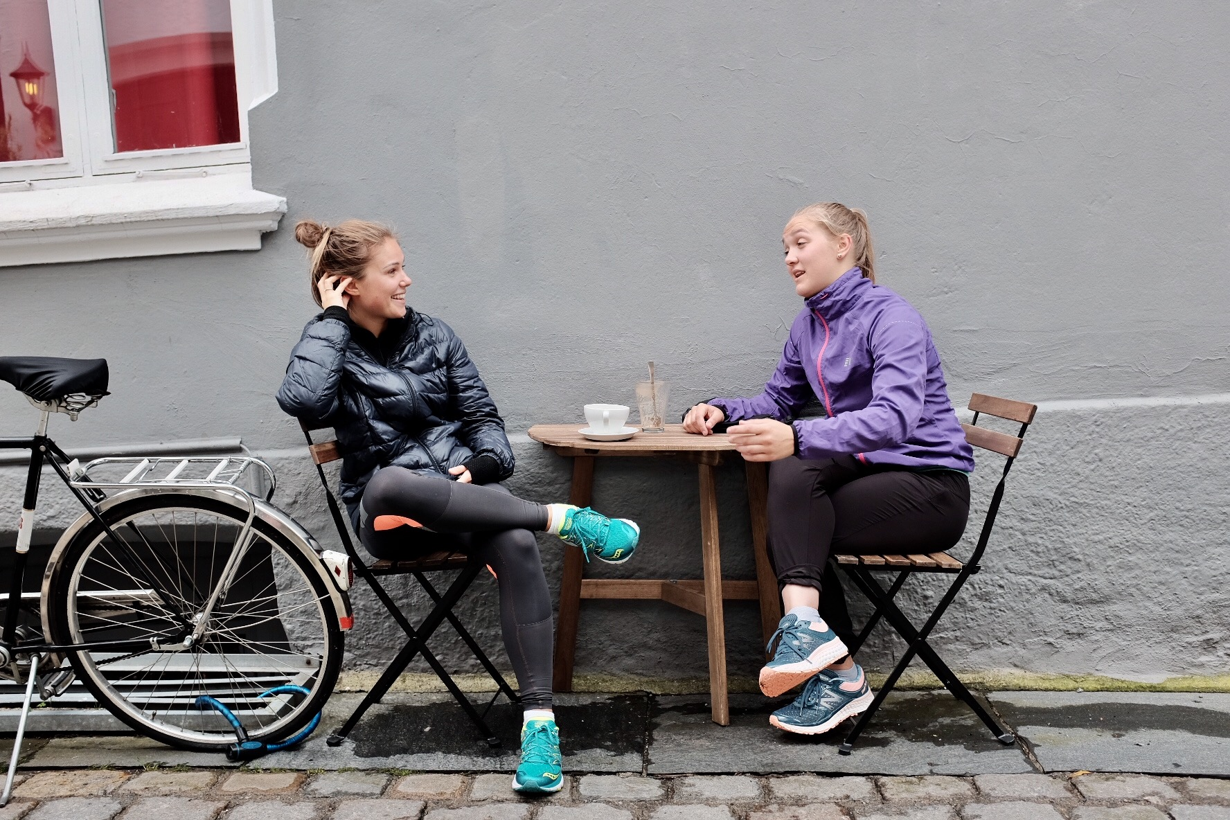 Two girls chatting it up at a local coffee joint.