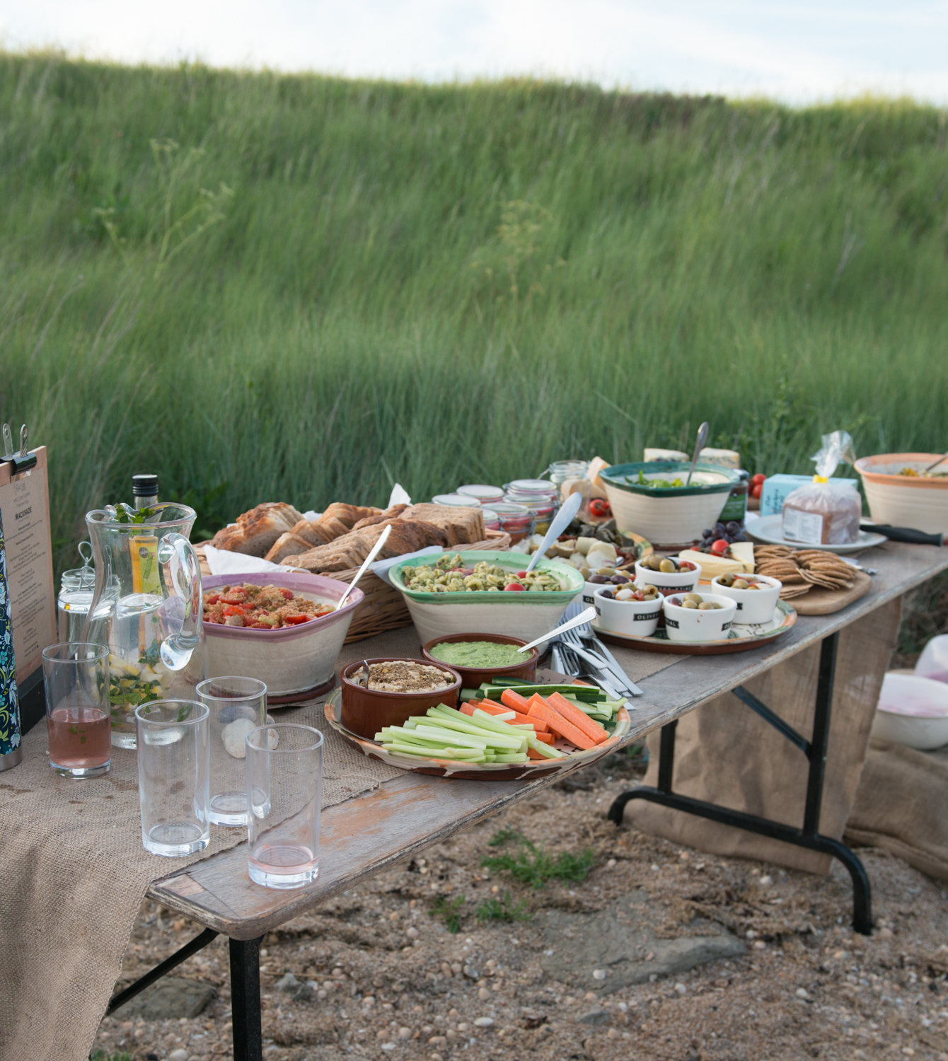 A beach picnic on wooden table with white windbreak behind it.