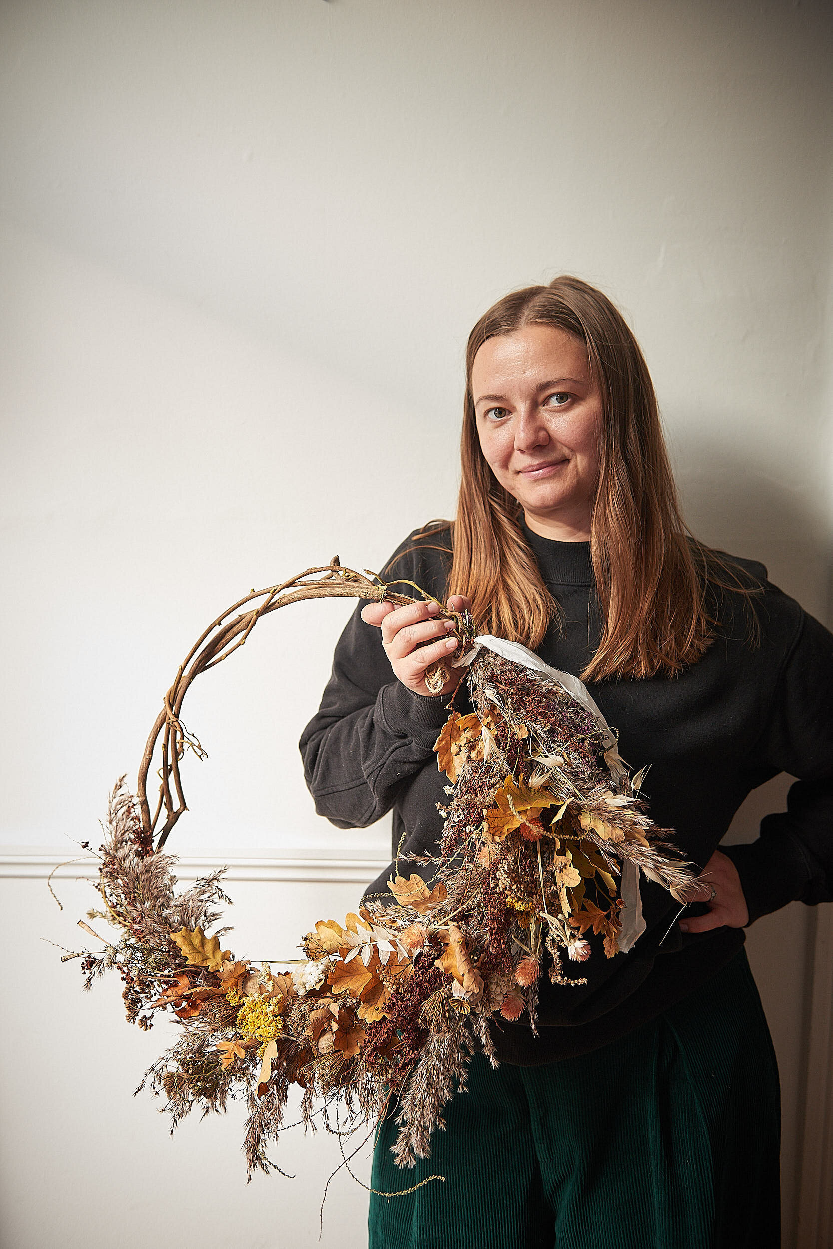10 wonderful things to make, do and celebrate in October! Hannah is holding a foraged Autumn wreath. It has a hand woven base and is half adorned with beautiful Autumnal  foraged leaves and seed heads.