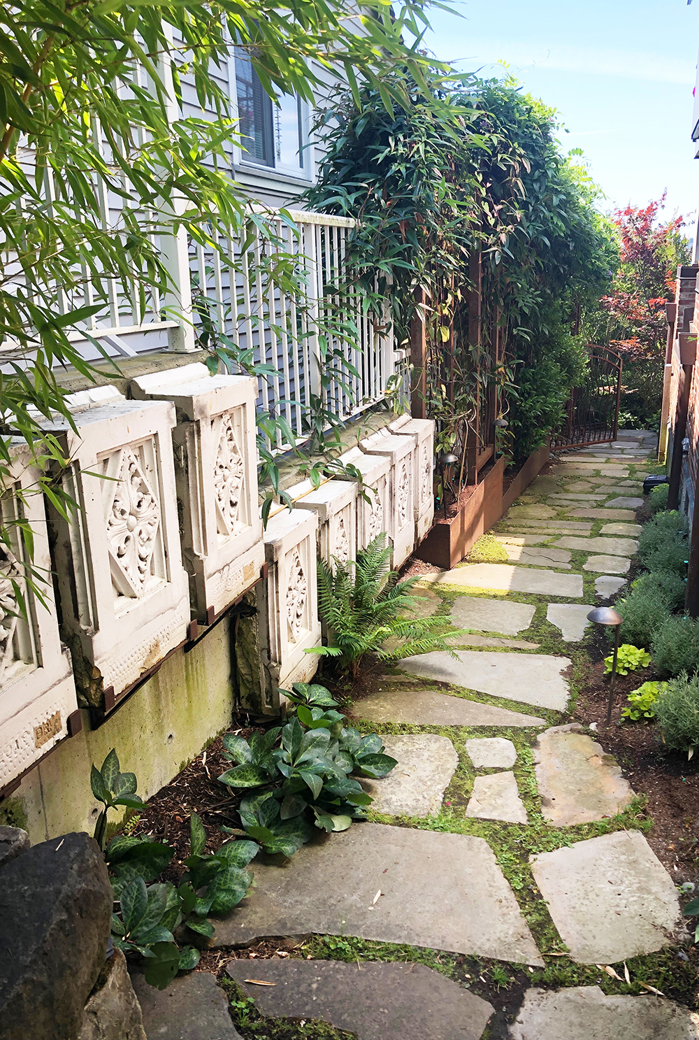 This Seattle garden tucked in some architectural artifacts to add charm to this narrow space