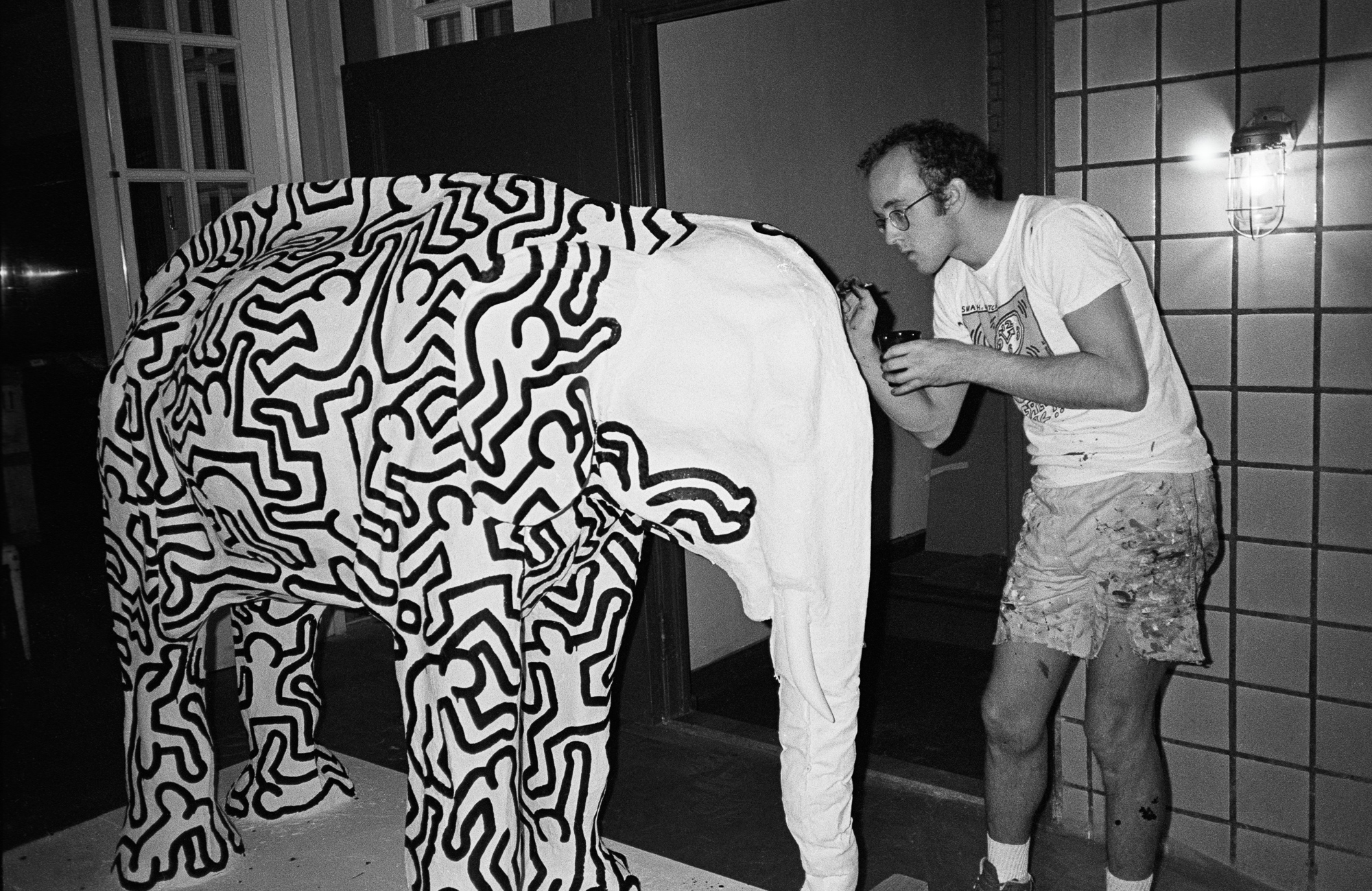 Keith Haring paints Andy Warhol's paper-mâché elephant. (1989)