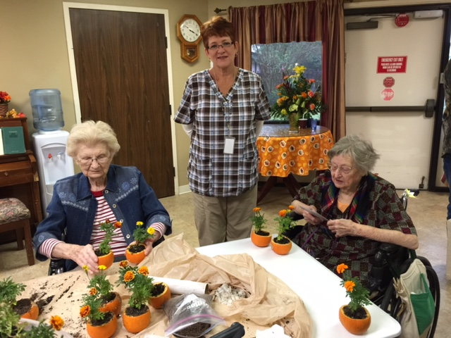 Residents of High Hope Care Center enjoy planting flowers in pumpkins.
