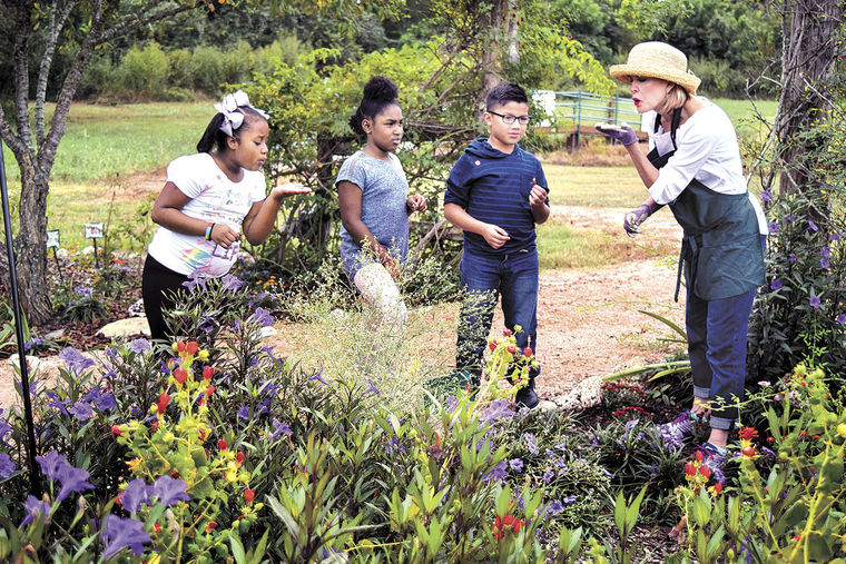 Member, Debbie Urquhart (right) shows how a plant spreads its seeds and has students Troytasia Briscoe, Zora Austin and Axel Lemus also try it Thursday morning in the Butterfly Garden at Brenham Elementary School. Garden club members and students were working on planting new plants for the butterflies in the garden. (Photo courtesy of  Brenham Banner Press )