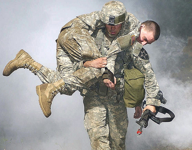 "Capt. Charles Moore, commander, Company C, 202nd Brigade Support Battalion, 4th Brigade, 2nd Infantry Division, performs the fireman's carry of a ""casualty"" during the nuclear, biological and chemical portion of the Expert Field Medical Badge training and testing here Sept. 14. Photo by Spc. Leah R. Burton. This photo appeared on   www.army.mil  . By  The U.S. Army  At  Flickr.   Licensed under  CC BY 2.0."