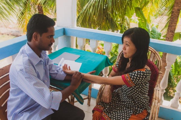Dr. Arun giving a pulse reading to one of our teachers, Tomoko