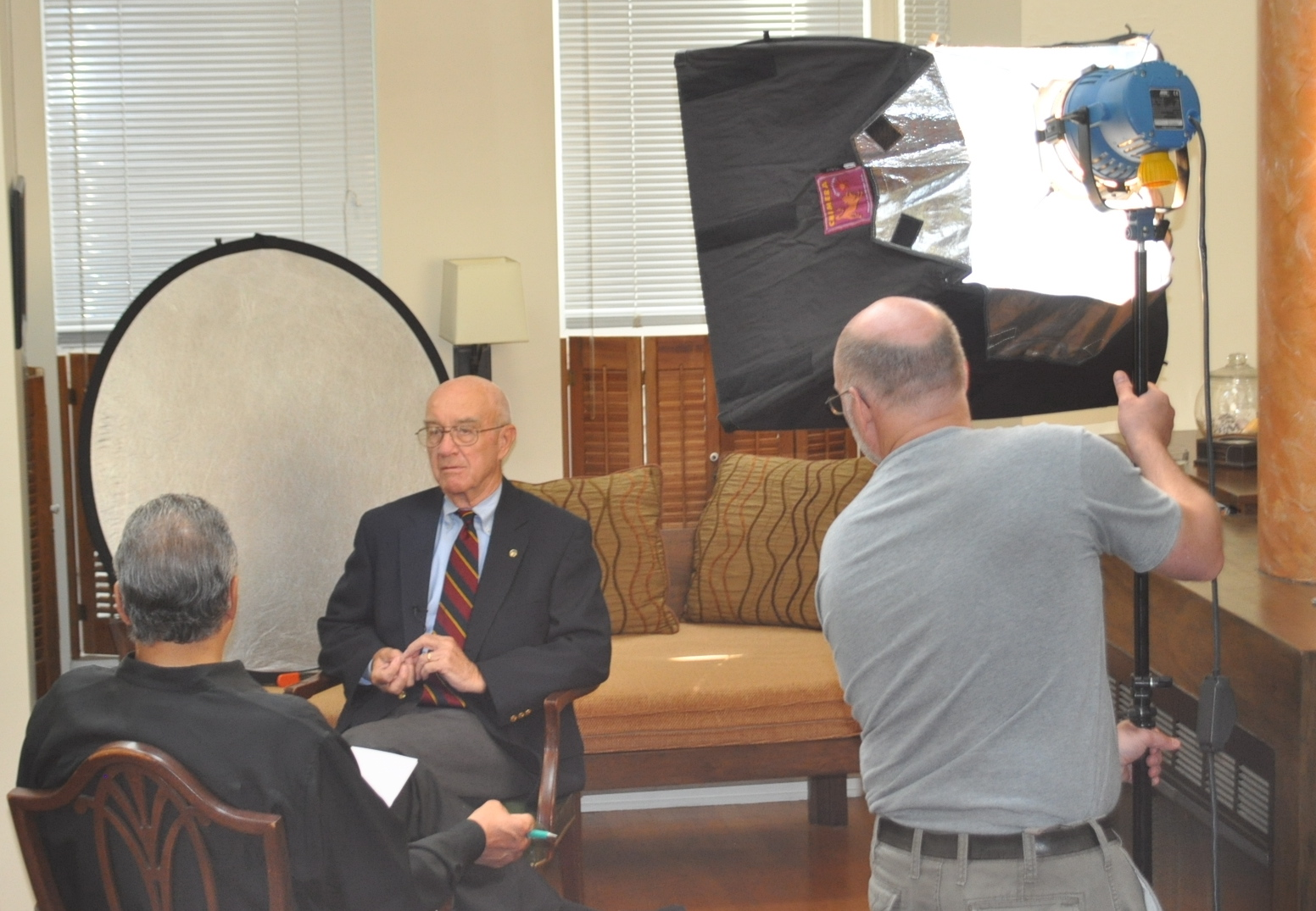William Braker is interviewed by Mark Rosenthal. Videographer Dave Monk adjusts the lighting.