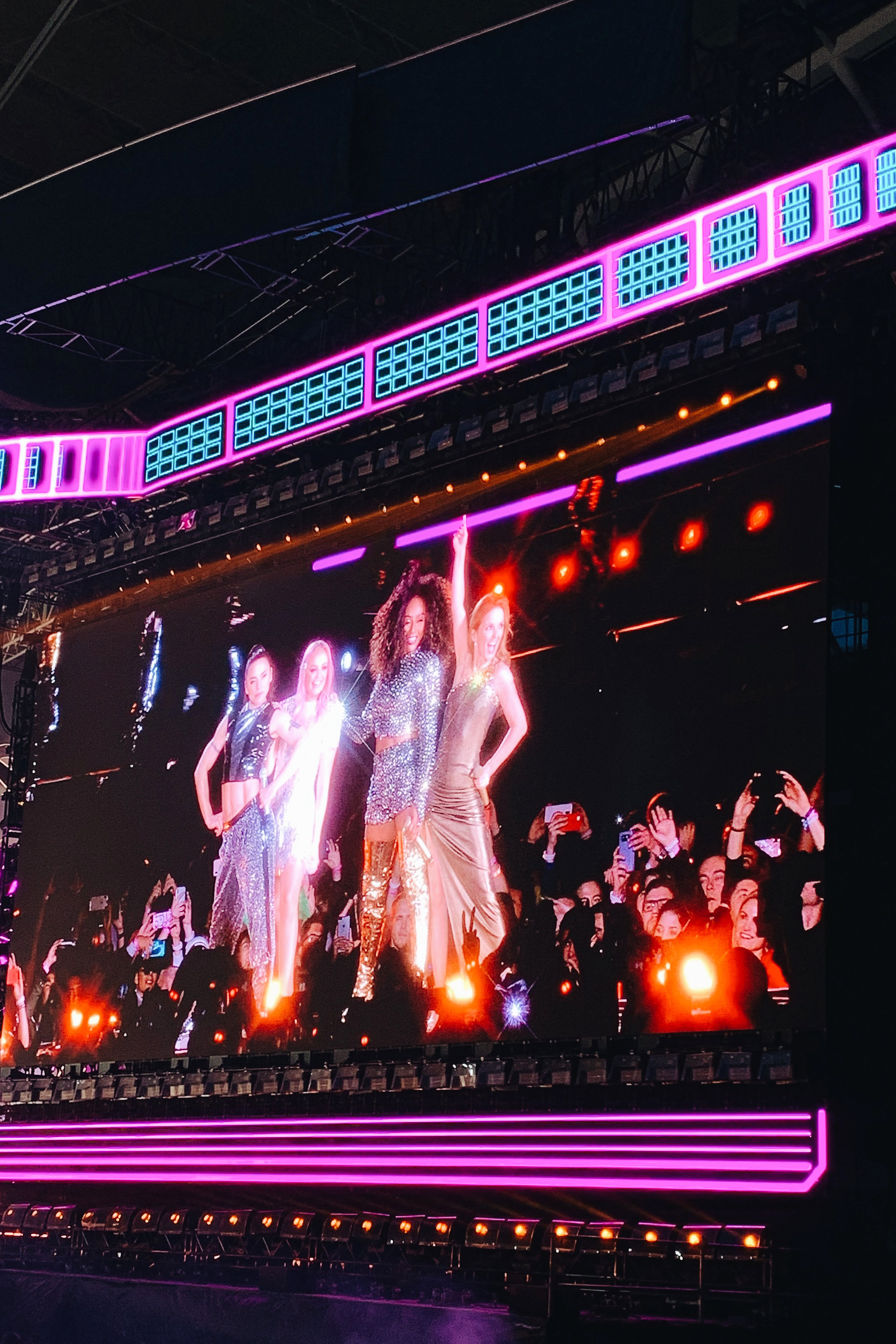 """- Once we got in, Lauren and I weren't all that fussed on seeing the support act, Jess Glynne, so we hung about chatting over a few drinks before we took our seats. When we did, I was in sheer awe at the size of the venue and it was incredible to watch it slowly pack out. With a crowd of 80,000 people, it was the biggest gig I've ever been to and the biggest gig I'll probably ever go to!Just before they came on stage, the show was introduced with the screens displaying, """"We welcome all countries of origin. All gender identities. All abilities. All ages. All sexual orientations. All races. All religions & beliefs. Welcome to Spice World"""" and then showed an array of flags from all different countries. It gave me goosebumps and I felt as if my heart could've exploded! It was so empowering and made me feel so proud to be a Spice Girls fan. Immediately after, the crowd roared as they opened with Spice Up Your Life and I felt like I was nine years old again!I was kind of expecting a nostalgia trip back to the '90s with the super short dresses, crop tops and platform shoes they used to perform in, but I suppose they needed to feel a little more comfortable on stage being in their forties now! Geri even poked fun at how much older they all were, but that they were doing this all for us! While their costumes were modernised and more grown up, it still felt like them and there were still a few outfits to take us back to the good old days. Geri's iconic Union Jack dress got a classy update as it became floor-length, Mel B wore plenty of leopard print and the outfits they wore while performing the closing song, Wannabe, were the same ones they wore in the music video, only more jazzed up and blingy!"""