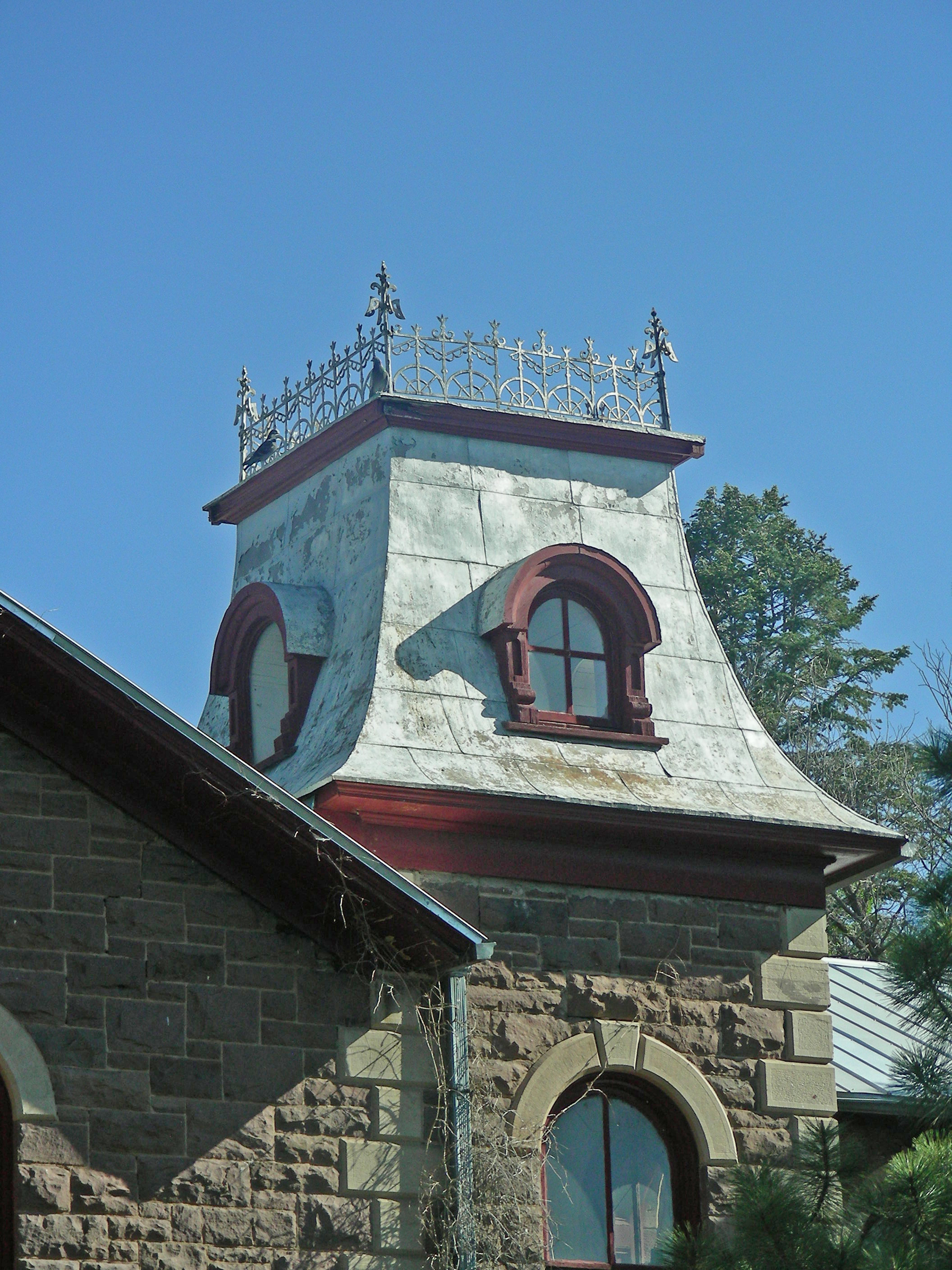 Original roof features such as this roof tower with iron cresting and wooden window molding add character, and warrant preservation.