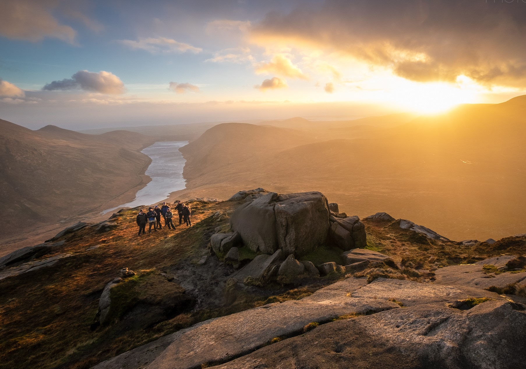 A workshop group experience a stunning sunset on the summit of Doan in the Mourne mountains
