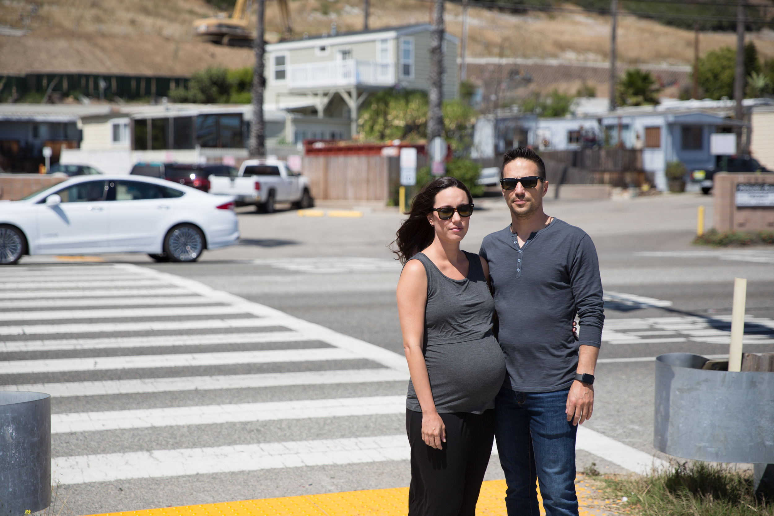 Michelle and Jon Brown stand at the crosswalk in front of the mobile home park they live in, where in 2015 Michelle and their family dog, Yogi, were tragically struck, killing Yogi and leaving Michelle with a three-inch scar on her forehead.