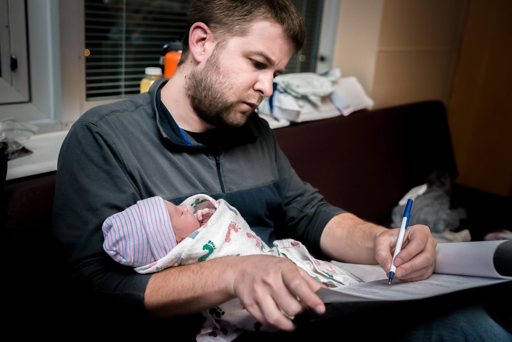 Swedish-Medical-Center-Denver-Dad-Fills-Out-Paperwork