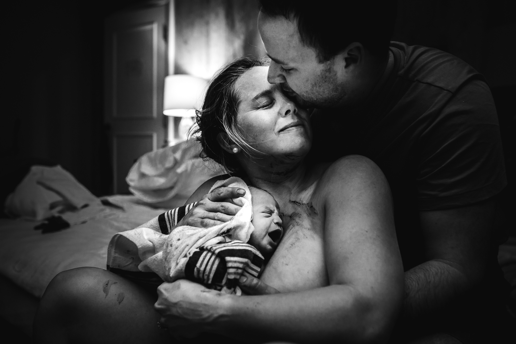 new-family-embraces-after-birth