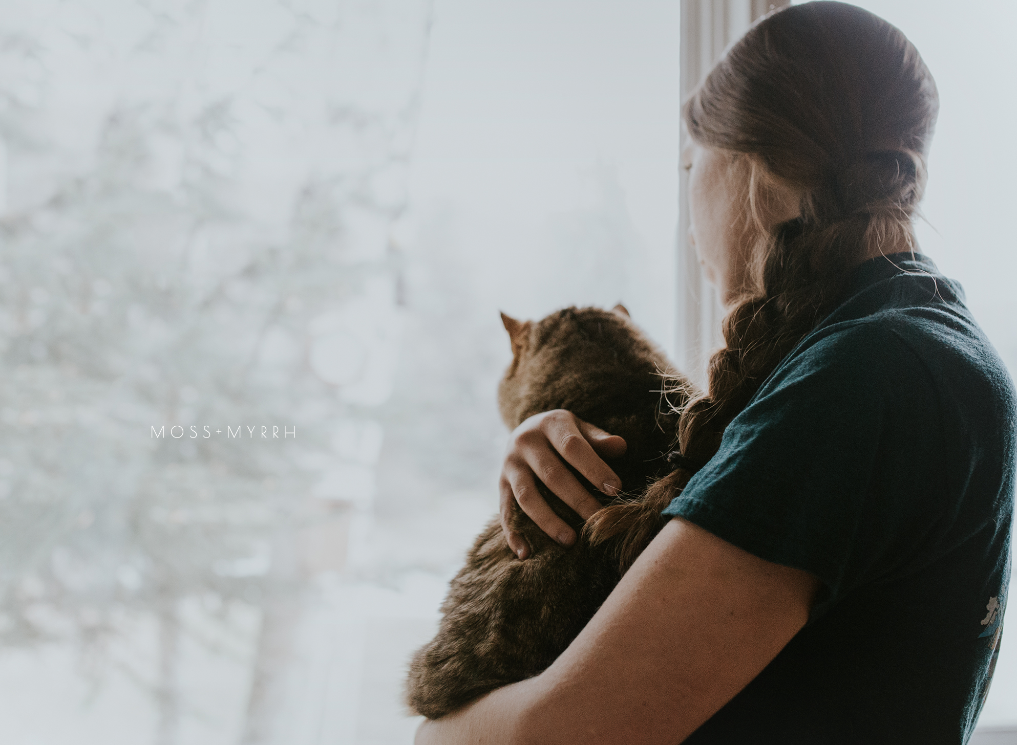 woman and cat looking out window